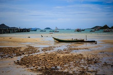 Small Wooden Fishing Boats Mooring At The Dirty Beach In Front Of Fisherman Village In Thailand On The Sunny Day