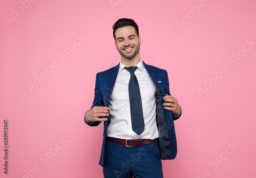 attractive young man smiling and holding coat on pink background Wallpaper Mural