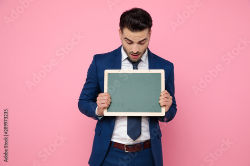 Photo  attractive young man holding an empty board on pink background