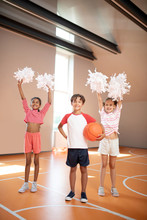 Girls Practicing Cheerleading Standing Near Classmate