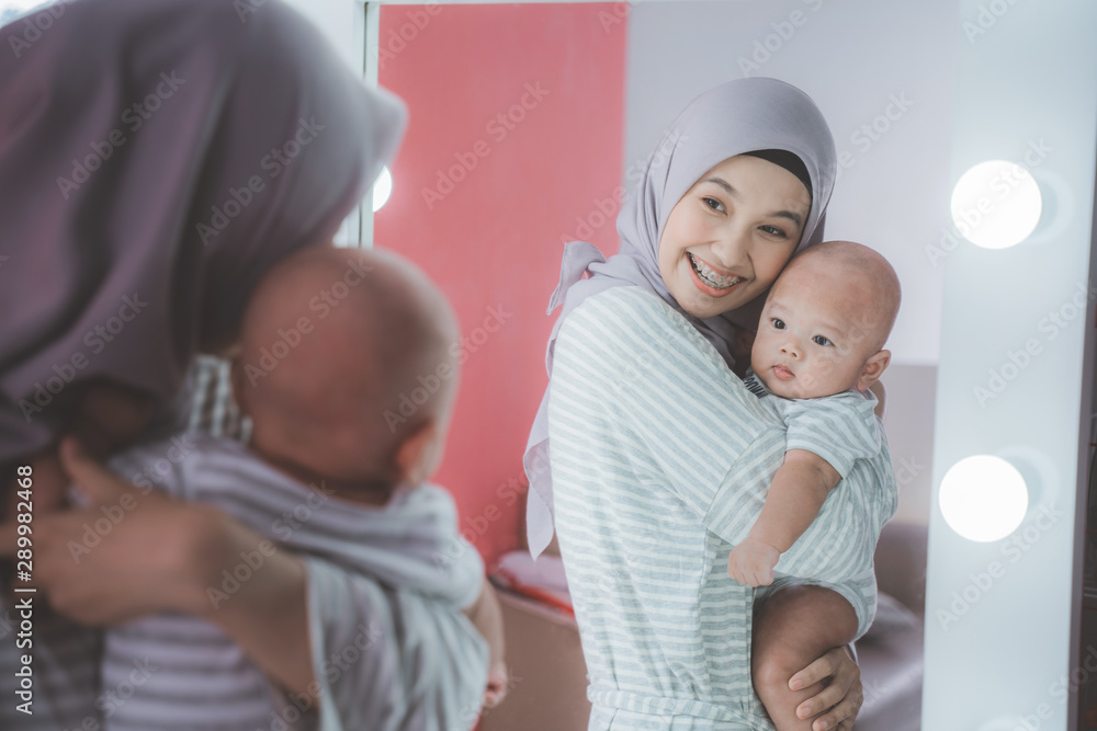 Fototapety, obrazy: muslim woman with hijab playing with her baby looking at the mirror
