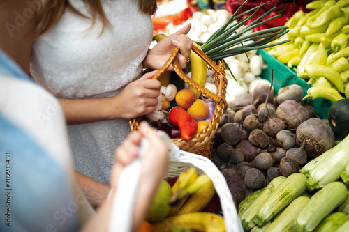 Fotografie, Obraz  Young woman buying vegetable on stall at the market