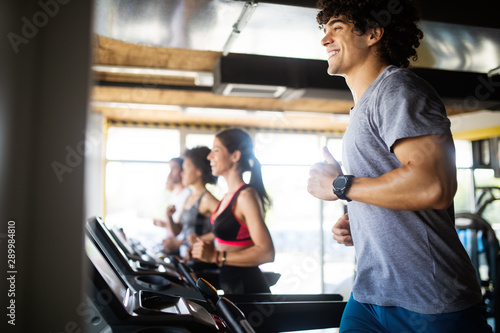 Group of young people running on treadmill in gym - 289984810