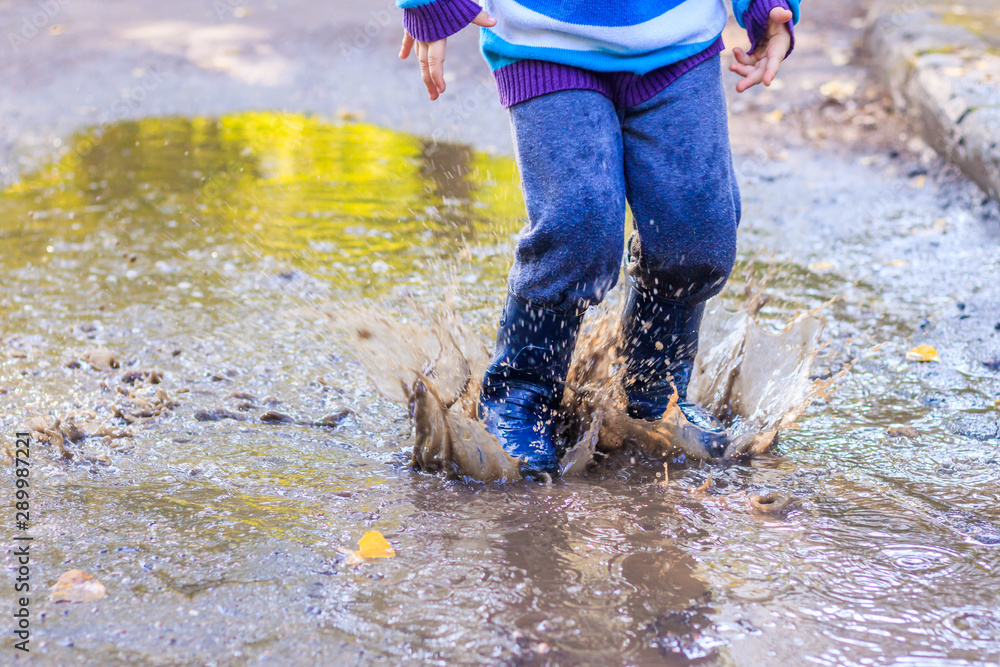 Fototapety, obrazy: A little boy is jumping in a puddle. A boy in rubber boots. Happy childhood. Puddles after the rain. Warm summer evening.