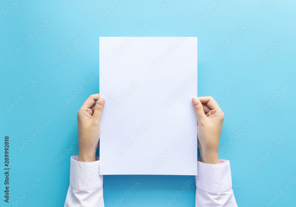 Fototapety, obrazy: close up hands holding  empty white blank letter paper size A4 for flyer or invitation mock up isolated on a blue background.