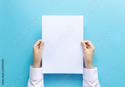 Fototapeta close up hands holding  empty white blank letter paper size A4 for flyer or invitation mock up isolated on a blue background. obraz