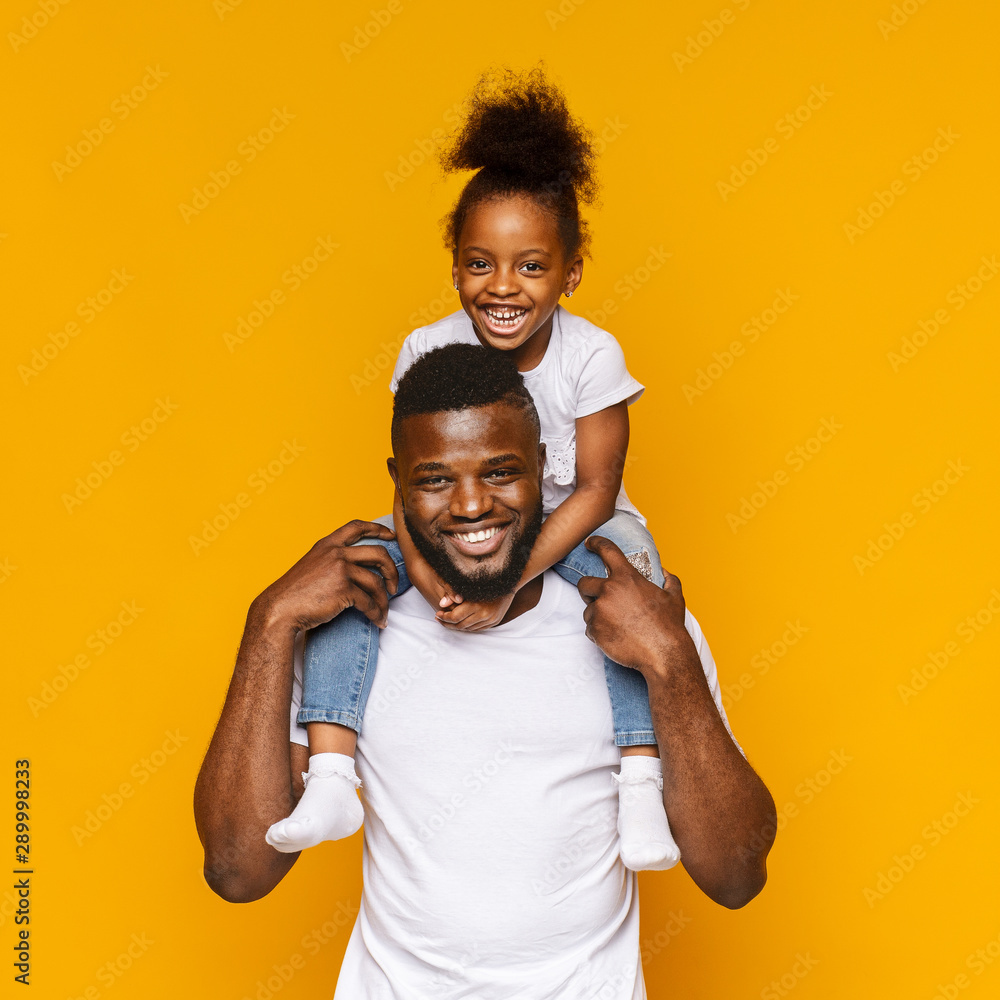 Fototapety, obrazy: Millennial african father riding his little daughter on shoulders