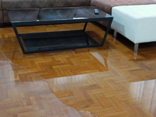 Water Spreading / Flooding On Living Room Parquet Floor In A House - Damage Caused By Water Leakage