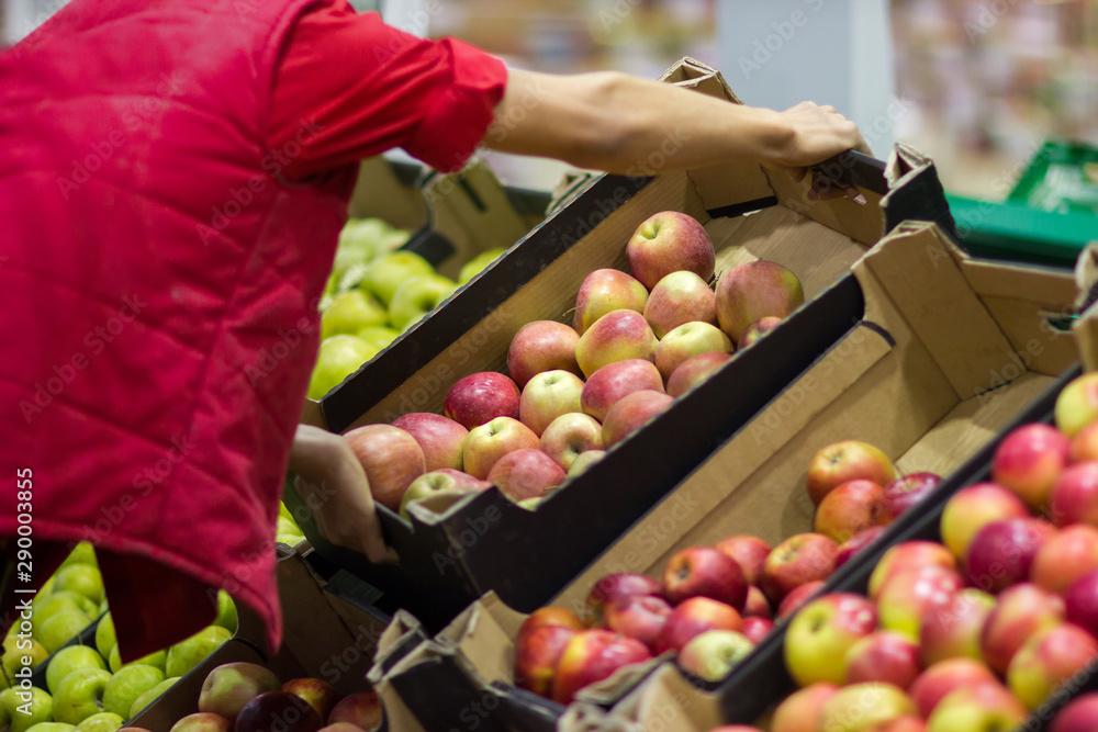 Fototapety, obrazy: Young man seller lays out fresh fruits of the box on the grocery store