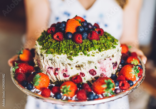 Woman presenting a birthday cake with fresh fruits. Healthy dessert - 290005482
