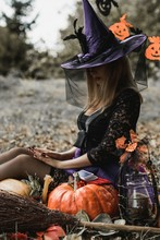 Halloween Holiday Witch Lady In Mystical Atmosphere With A Pumpkin Outdoors, Celebrate Autumn