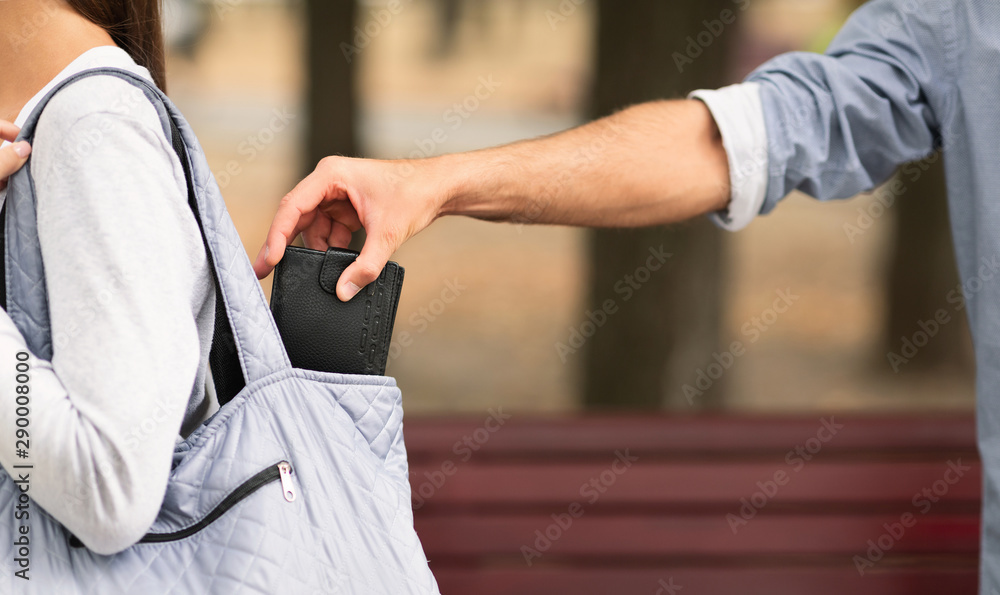 Fototapeta Pickpocket thief stealing wallet from woman handbag