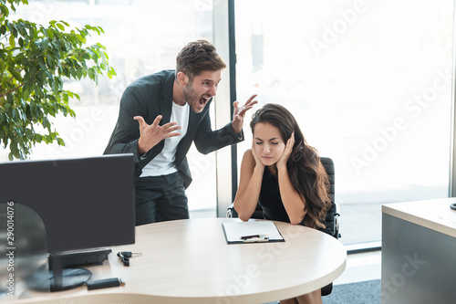 Photo strict boss man swearing at depressed employee woman for bad work at the workpla