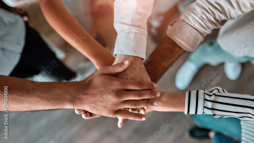 Obraz We are strong. Top view of business people holding hands together while standing in the office - fototapety do salonu