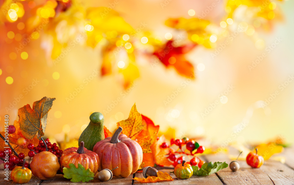 Fototapeta Autumn background from fallen leaves and pumpkins on wooden vintage table. Autumn concept with red-yellow leaves background. Thanksgiving pumpkins.