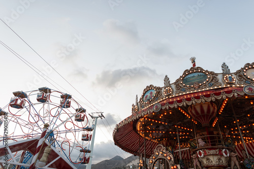 Carta da parati  View on vintage beautiful carousel with bright lights with orange bulbs and on a ferris wheel