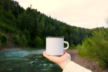 Woman Holding Enamel Mug With Riverside View