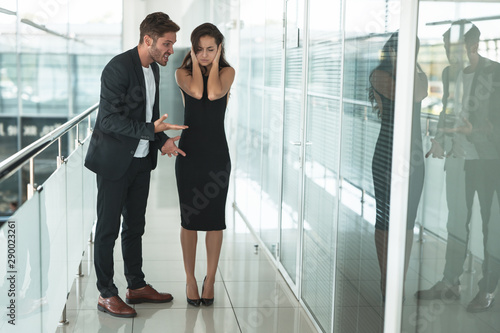 two colleagues angry man and exhausted upset woman having a professional argument at workplace