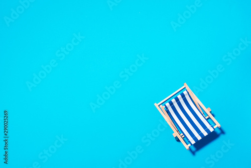 Flat lay of beach deck chair on blue background with copy space. Summer and travel concept. Creative banner
