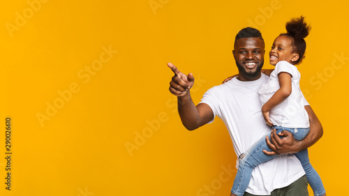 Obraz Cheerful african man showing something to his little daughter - fototapety do salonu