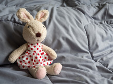 A Rabbit Doll Wearing A Red Polka Dot Dress Sitting On The Bed