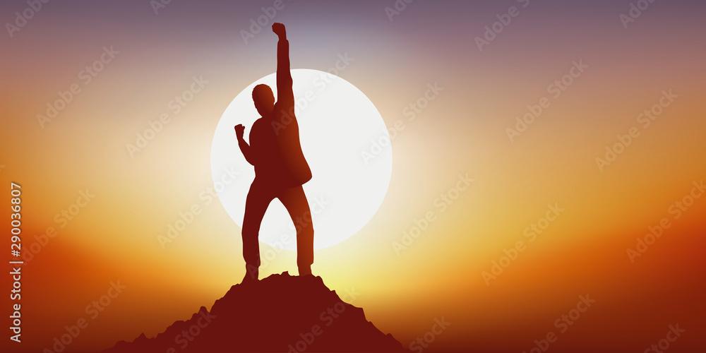 Fototapeta Concept du leadership avec un homme qui exprime sa joie en levant le point en signe de victoire en atteignant le premier le sommet d'une montagne