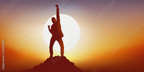 Fototapeta Concept du leadership avec un homme qui exprime sa joie en levant le point en signe de victoire en atteignant le premier le sommet d'une montagne obraz