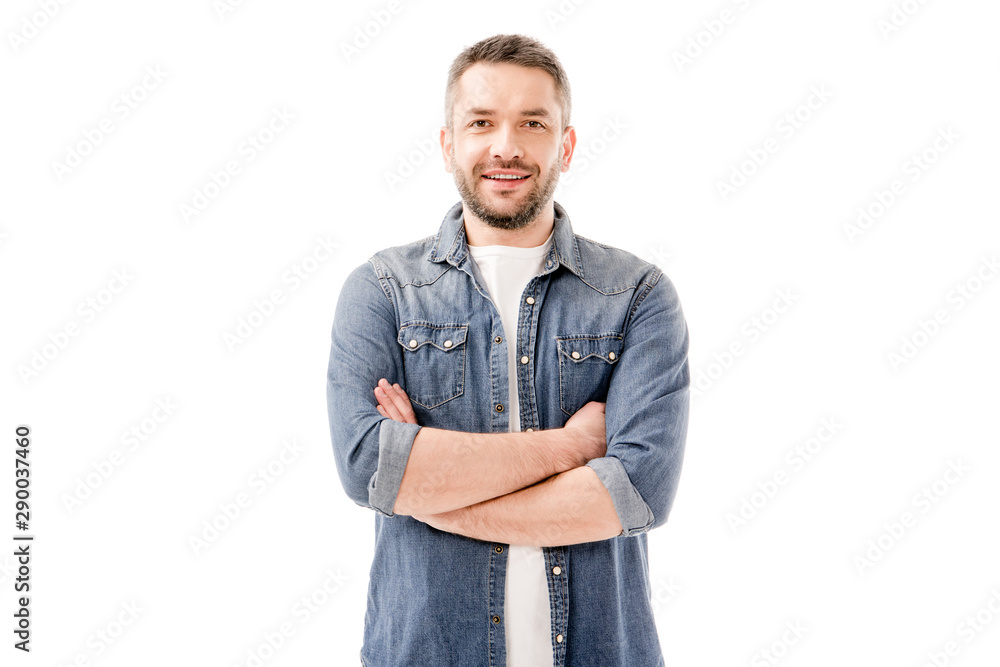 Fototapeta front view of smiling bearded man in denim shirt standing with crossed arms isolated on white