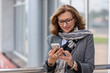 Leinwanddruck Bild - Portrait of a smiling business woman in glasses looking at mobile phone