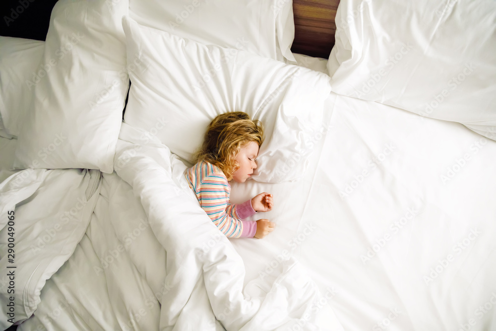 Fototapeta Cute little toddler girl sleeping in big bed of parents. Adorable baby child dreaming in hotel bed on family vacations or at home.