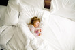 Cute little toddler girl sleeping in big bed of parents. Adorable baby child dreaming in hotel bed on family vacations or at home.