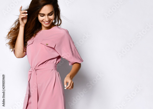 Foto Full length portrait of happy beautiful woman in pink dress posing in studio iso