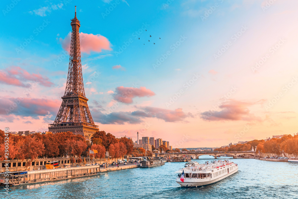 Fototapeta The main attraction of Paris and all of Europe is the Eiffel tower in the rays of the setting sun on the bank of Seine river with cruise tourist ships