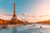Fototapeta Fototapety z wieżą Eiffla - The main attraction of Paris and all of Europe is the Eiffel tower in the rays of the setting sun on the bank of Seine river with cruise tourist ships