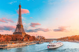 Fototapeta Wieża Eiffla - The main attraction of Paris and all of Europe is the Eiffel tower in the rays of the setting sun on the bank of Seine river with cruise tourist ships