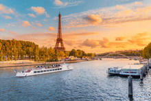 The Main Attraction Of Paris And All Of Europe Is The Eiffel Tower In The Rays Of The Setting Sun On The Bank Of Seine River With Cruise Tourist Ships