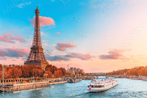 Photo Stands Eiffel Tower The main attraction of Paris and all of Europe is the Eiffel tower in the rays of the setting sun on the bank of Seine river with cruise tourist ships