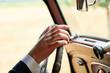 Driver keeps hand on steering wheel of his vintage car.