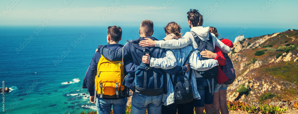 Fototapeta A company of young happy friends travels in Portugal, stands on the shore of the Atlantic Ocean and hugs, travell together, community friendship vacation