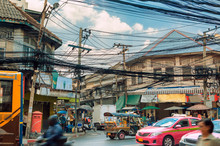 Bangkok Street.Lifestyle And Street Environment In Bangkok, Thailand. Traffic Tuk Tuk, Pink Taxis And Traditional Buses. Tangle Of Electric Cables And House Facades