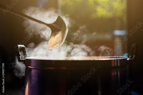 Cooking person in the restaurant is cooking while using the dipper in a large pot Fototapeta