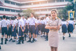 Smiling female high school teacher in Thai government teacher uniform is standing among students, Thailand, southeast Asia.