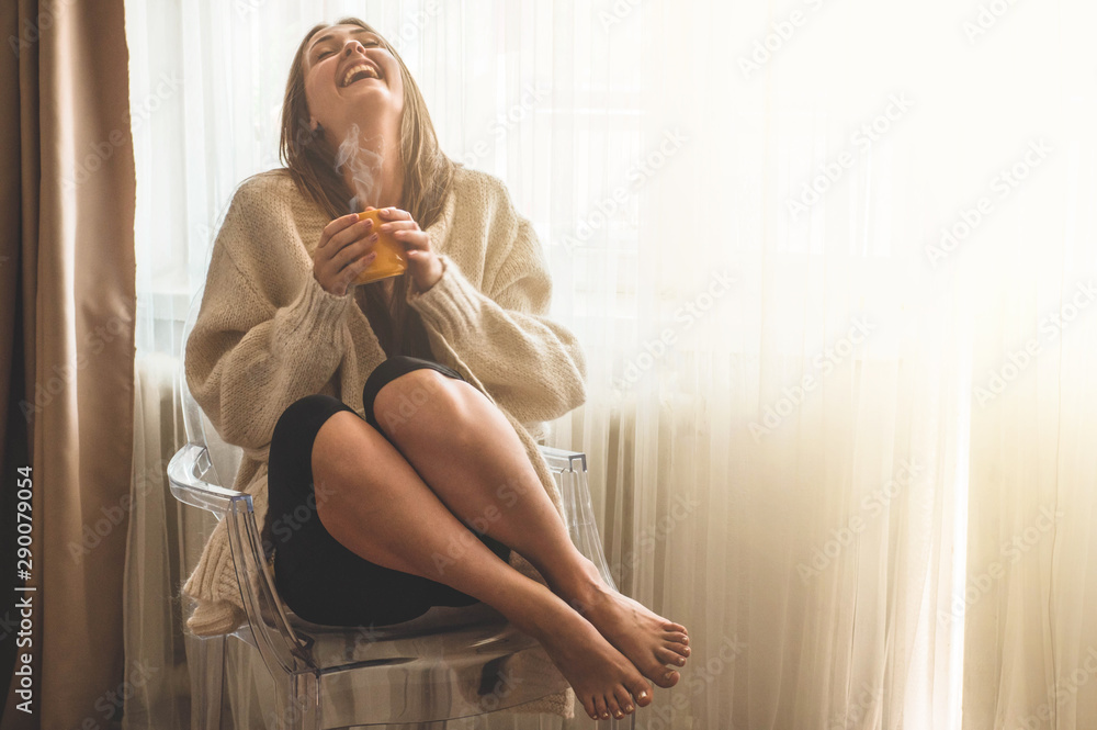 Fototapeta Woman with cup of hot drink by the window. Looking at window and drink tea. Good morning with tea
