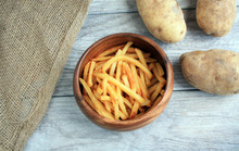 Wooden Bowl Of French Fries And Three Loose Potatoes. Burlap Bag On The Side. On A Gray Wooden Background