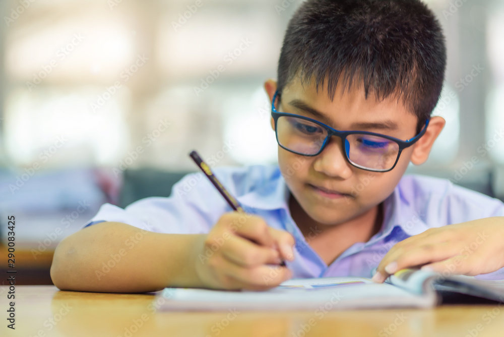 Fototapety, obrazy: Asian elementary school boy in a white school uniform and wearing glasses, is studying in the classroom.