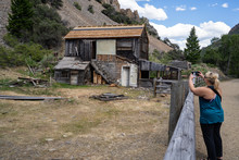 Woman Tourist Takes Photos With A Phone Of The Abandoned Buildings In The Bayhorse Ghost Town In Idaho