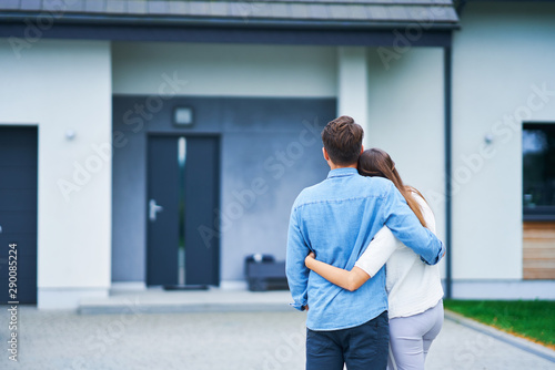 Couple in front of one-family house in modern residential area - fototapety na wymiar