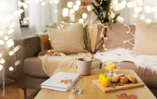 hygge and cozy home concept - cup of tea with lemon, book, autumn leaves and oat Tablou Canvas