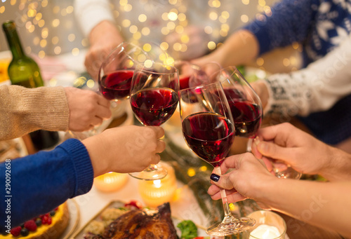 Acrylic Prints Wine holidays and celebration concept - close up of friends having christmas dinner at home, drinking red wine and clinking glasses