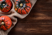 Flat Lay View Of Three Pumpkins On Jute Bag. Old Wooden Background Or Table Top